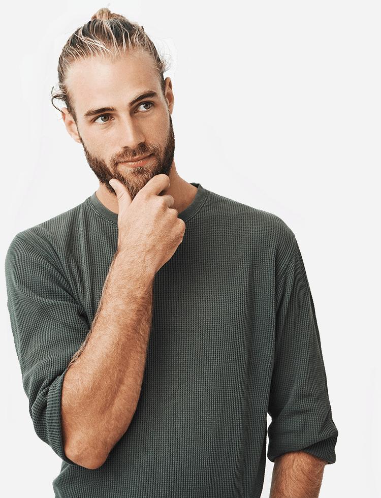 mężczyzna w szarej bluzie trzymający się za brodę