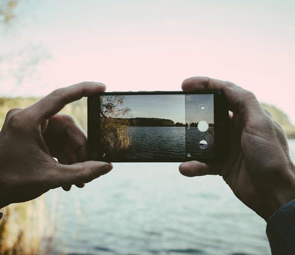 mężczyzna robiący zdjęcie telefonem jeziora
