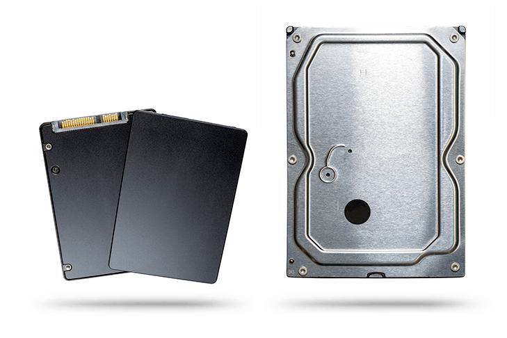 dwa czarne dyski SSD obok srebrnego dysku talerzowego HDD